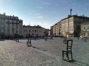 Der zentrale Platz in Podgorze. Von hier wurden bei der Ghettoauflösung 1943 sämtliche Juden deportiert. Die arbeitsfähigen kamen ins nahe gelegene Lager Plaszow. Alte, Frauen, und Kinder wurden direkt zur Vernichtung in die Lager Belzec und Auschwitz überstellt. Künstler stellten auf dem Platz 33 übergroße Metallstühle und 37 kleinere Kopien dieser Stühle auf, die zum Hinsetzen einladen. Sie symbolisieren die Tragödie der Ghettobewohner, von denen nur Möbel übriggeblieben sind, und sie symbolisieren zugleich ihre letzte Reise.